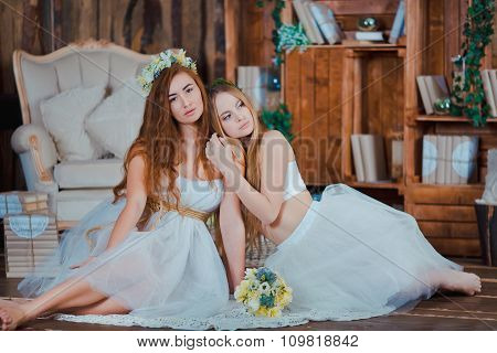 Two beautiful sensual brides sitting in vintage interior holding flowers