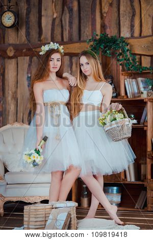 Two beautiful sensual brides standing in vintage interior holding flowers wearing white dress