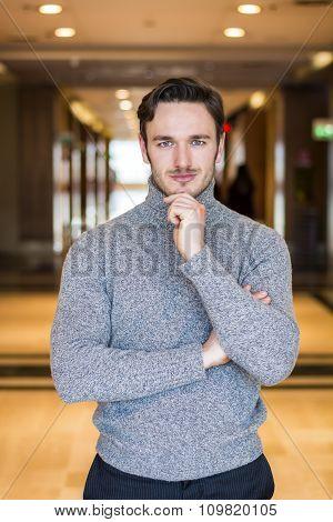 Handsome serious man standing inside modern building