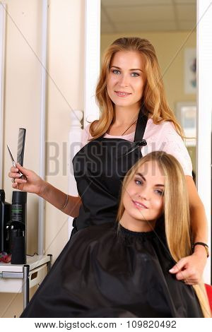 Beautiful Blonde Female Hairdresser Holding Scissors And Comb In Hands