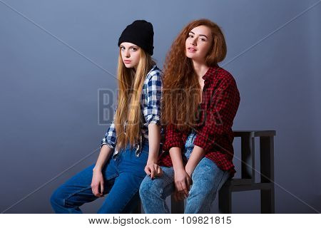 Two beautiful sexy young girls in jeans sitting. Fashion portrait of girlfriends on grey background