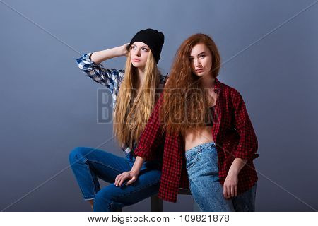 Two beautiful sexy young girls in jeans. Fashion portrait of girlfriends on grey background