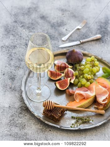 Wine appetizer set. Glass of white wine, honeycomb with drizzlier, figs, grapes, melon and prosciutt