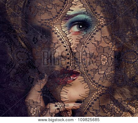 portrait of beauty young woman through lace close up mistery