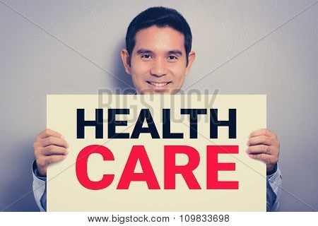 A Man With Smiling Face Showing Health Care Sign