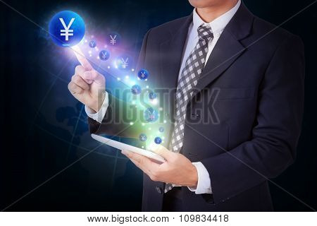 Businessman holding tablet with pressing yen sign icon button. internet and networking concept