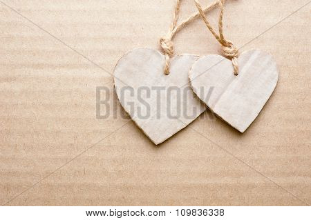 Couple Of Cardboard Cutted Hearts Against Striped Cardboard Sheet