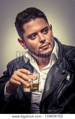 Elegant man with black leather jacket drinking a whiskey in studio
