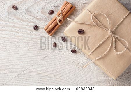 Gift Box Decorated Coffee Beans And Cinnamon On White Wooden Table With Space