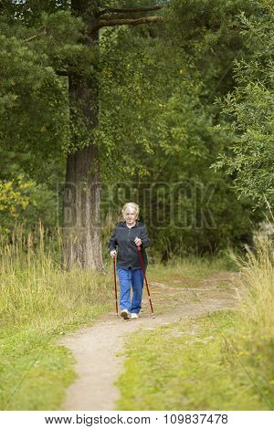 Elderly woman is engaged in Nordic walking in the Park.