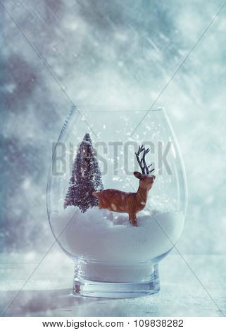 Reindeer Christmas scene in glass snow globe with blue cold tone