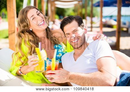 Woman and man with drinks in beach bar on lake