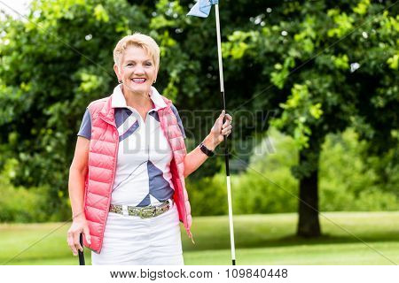Senior woman playing golf on course holding flag