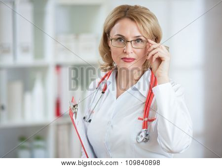 Serious pharmaceutist woman in glasses looking at camera