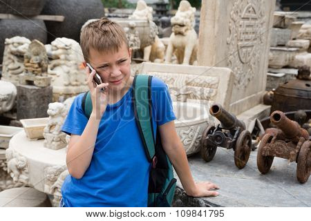Boy backpacker talking on mobile phone on the famous Panjiayuan Antique Market