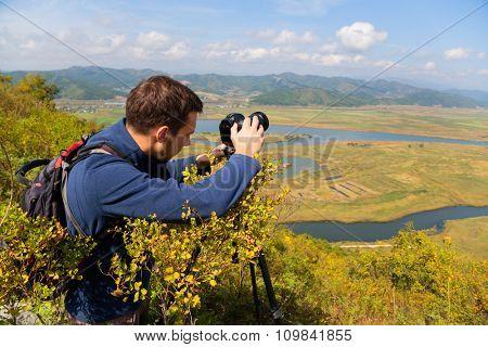 Photographer on top of mountain on the camera shoots neighborhood