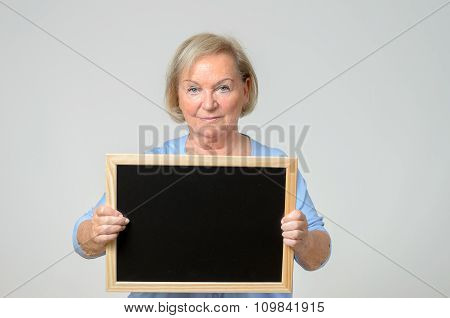Enthusiastic Senior Woman Holding A Blackboard