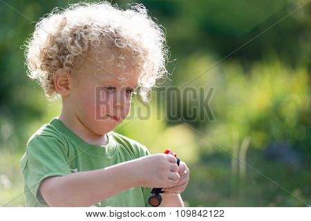 Little Blond Boy Playing With A Small Car