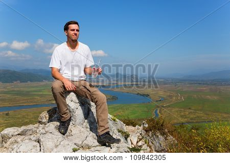Hiker drinks water from a bottle on top of the mountain.