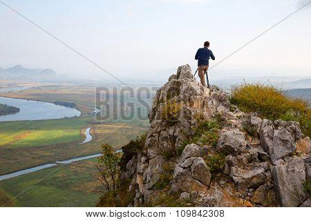 Photographer on top of mountain on the camera shoots neighborhood.