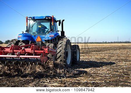 Farmer On A Tractor Plowed Field