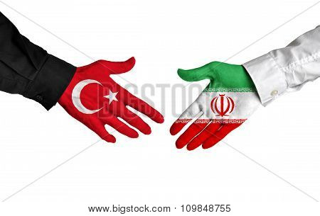 Turkey and Iran leaders shaking hands on a deal agreement