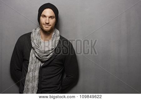 Casual young man standing against grey wall, smiling. looking at camera.