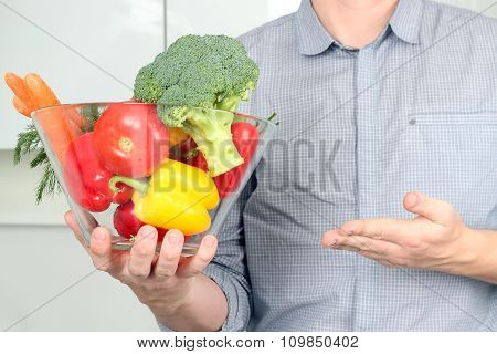 Man Holding Glass Dish With  Fresh Vegetables In The Kitchen