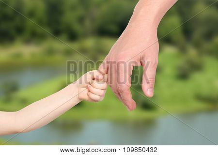 A Father  Holds The Hand Of A Small Child On A Green  Background