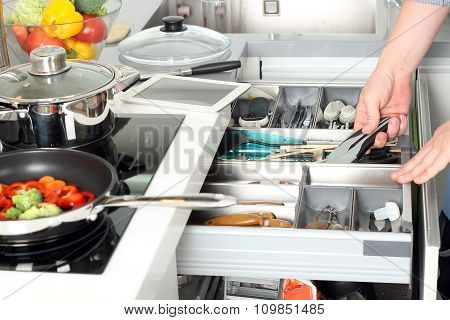 Man Take Off A Stainless Tool  In The Kitchen . Vegatables Behind