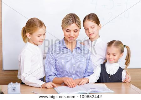 Teacher surrounded by her pupils.