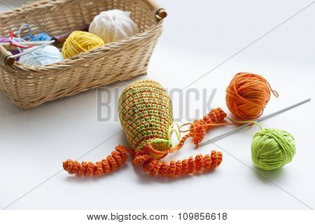 Making of handmade colorful crochet toys sweets (key ring) with skein on wooden table. Selective foc