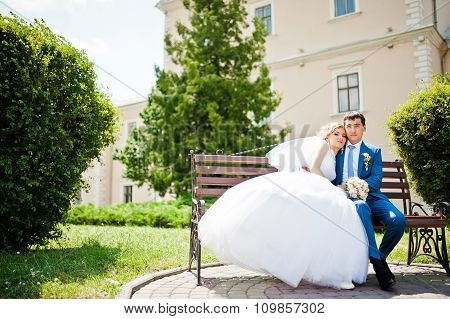 Wedding Couple In Love Sitting On Bench
