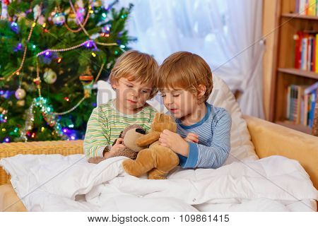 Two little sibling boys playing toys on Christmas