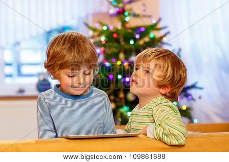 Two happy little kids playing with tablet pc, indoors