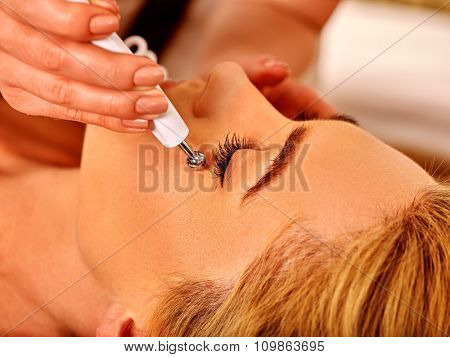 Close up of  woman receiving electric facial eyes massage on microdermabrasion equipment at beauty salon.