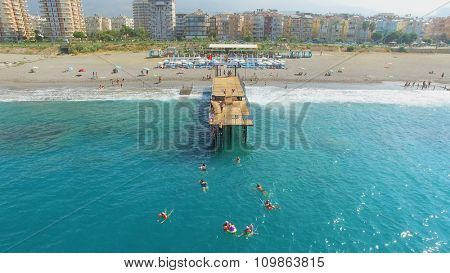 ALANIA - AUG 19, 2015: Many people swim in sea near pier on city beach at summer sunny day. Aerial view videoframe