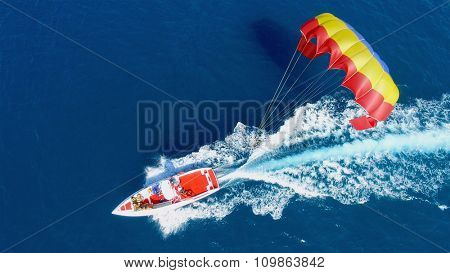 ALANIA - AUG 19, 2015: People fly on parachute attached to motorboat with group of tourists at summer sunny day. Aerial view videoframe