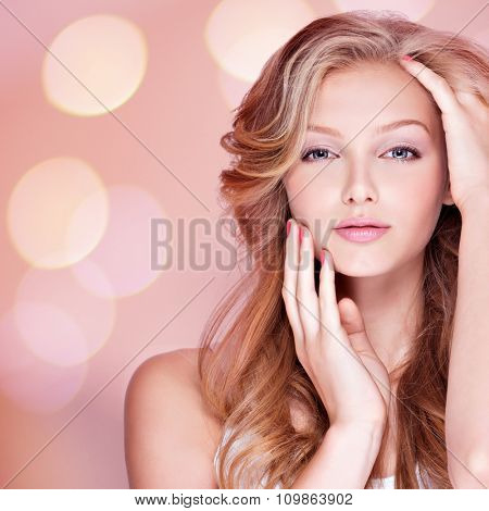 Portrait of beautiful young woman with long curly hair touching her face. Fashion model posing at studio