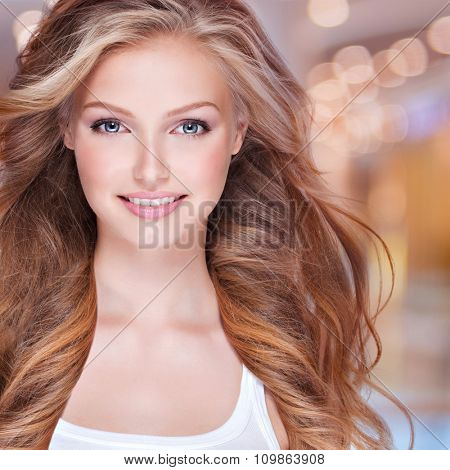 Portrait of beautiful happy young woman with long curly hair. Face of a smiling pretty model looking at camera