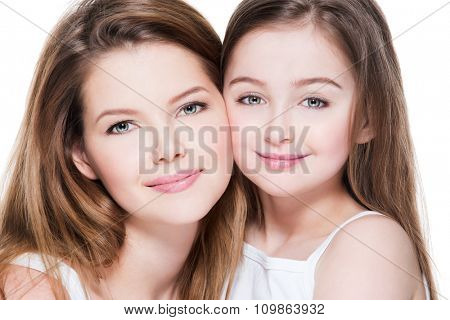 Beautiful and happy young mother with a small daughter 8 years embrace each other at studio