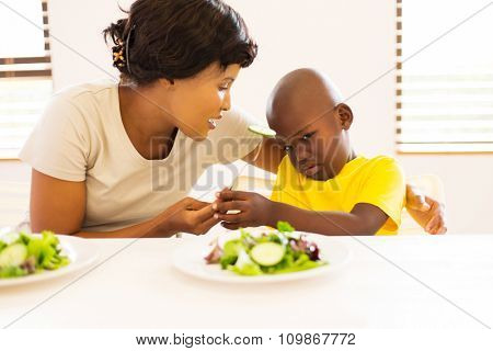 beautiful african mother asking her son to eat vegetables