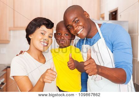 happy young african family giving thumbs up in kitchen