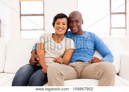 lovely young african couple relaxing on couch at home