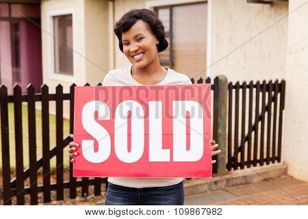 cheerful african american woman holding sold sign outside her house