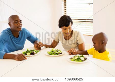 young african family praying before having meal at home