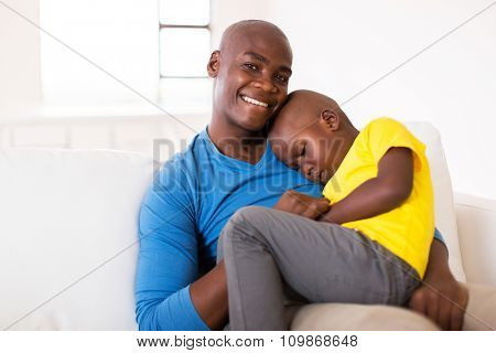 loving father sitting on the couch with his cute son