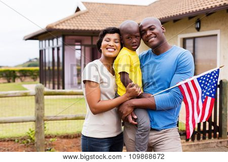 portrait of young family holding american flag outside their house