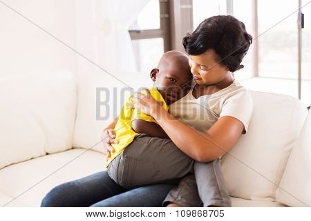 african american mother hugging her son at home
