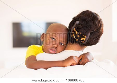 rear view of african woman holding her adorable son at home